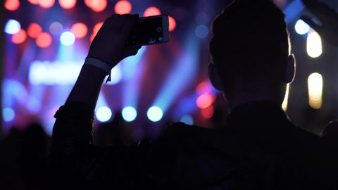 Happy man dancing and shooting video on smartphone at night club, concert Footage