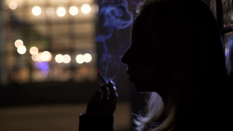 Female silhouette standing on the street and smoking cigarette, melancholy Footage