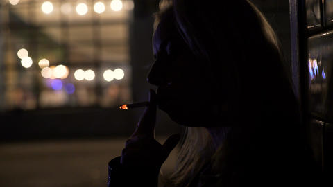 Silhouette of lonely woman inhaling cigarette smoke and thinking about problems Footage