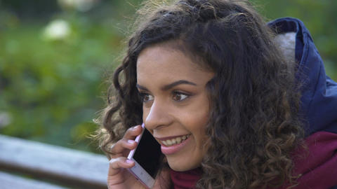 Curly biracial woman actively talking over smartphone, conversation with friend Footage