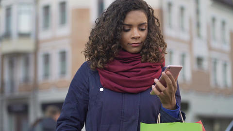 Pretty woman choosing gifts online, browsing sales in web stores on smartphone Footage
