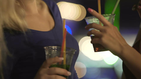 Two female friends in sexy dresses drinking cocktails and dancing in nightclub Footage