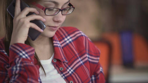 Pretty female in eyeglasses talking on smartphone, reading book, communication Footage