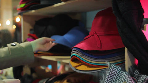 Young woman choosing hats from large seasonal assortment at department store Footage