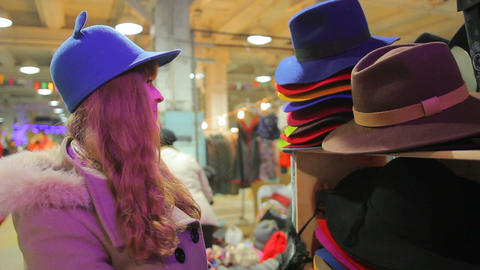 Female customer putting cute funny hat on, having fun in department store Footage