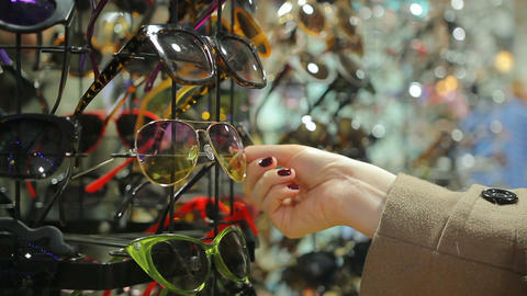 Woman choosing sunglasses from large collection displayed on shopping stand Footage