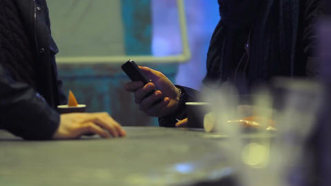 Friends hanging out at bar, drinking coffee and browsing Internet on smartphones Footage