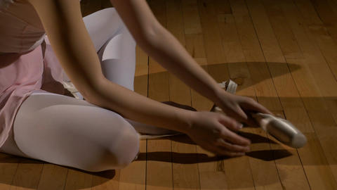 Dancer takes off ballet shoes and rubs her feet Footage