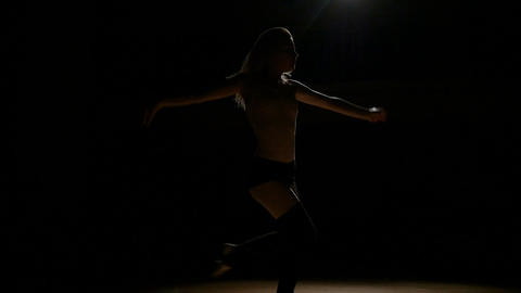 Silhouette of a sexy attractive woman dancing in the dark Footage