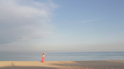 Girl in orange dress says good bye to the sea and walking... Stock Video Footage