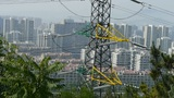 High-voltage wire tower in urban city,wind tree,distant mountain & hill Footage