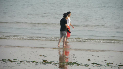 Couple at beach.Photographer taking pictures.Female model to pose.tide,tidal Footage