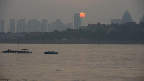 The sun goes down.Dusk waterfront.Ship boat on the sea,horizon is high-rise buildings Footage