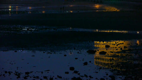 Tourist play at sand beach.Neon house reflection in... Stock Video Footage