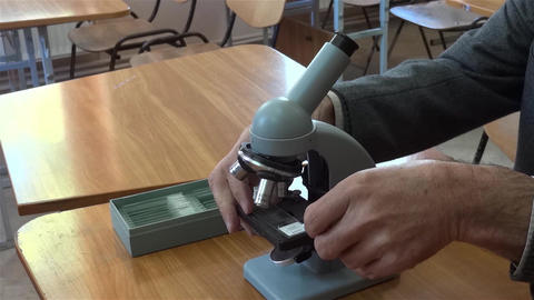 Teacher takes a blade with a preparation that fixed in the support microscope Footage