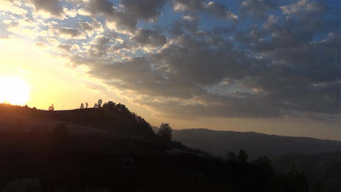 Sun at sunset over wooded hills and shrouded in shadow Footage