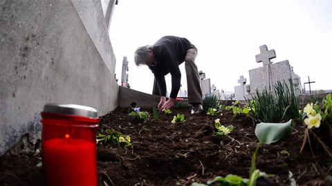 Man planted flowers on the grave of relatives of his and red candle is lit 2 Footage