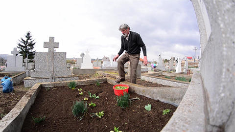 Man planted flowers on the grave of relatives of his and red candle is lit 4 Footage
