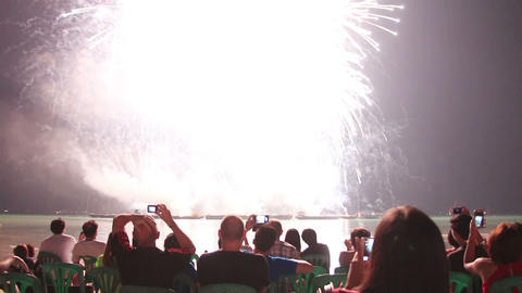 people sitting at beach and watching fireworks Footage