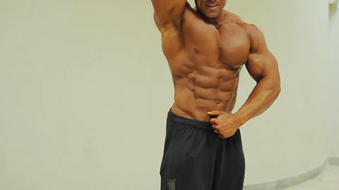 Confident male showing muscular body, bodybuilder posing at camera, sport Footage