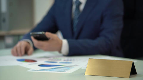 Busy man in suit using phone, documents on table, blank nameplate template Footage