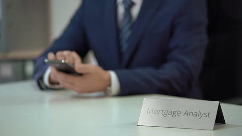 Professional mortgage analyst texting on smartphone, consulting client online Footage