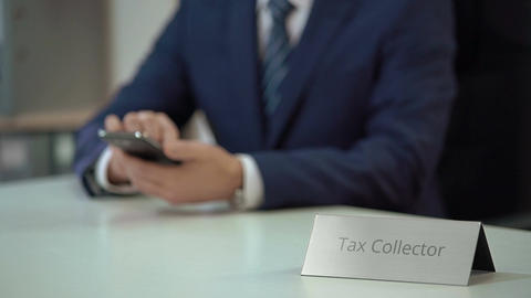 Busy male tax collector typing and sending messages to debtors from smartphone Footage
