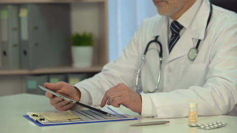 Male doctor consulting patient online, checking diagnosis on tablet in clinic Footage
