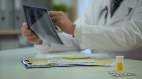 Therapist analyzing patient's lungs x-ray and writing down diagnosis, treatment Footage
