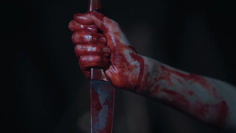 Fanatic's hands covered with blood holding murder weapon, human sacrifice, fear Footage