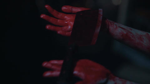 Nervous murderer with trembling hands dropping bloody butcher knife, horror Live Action