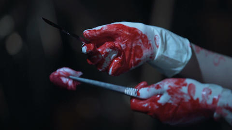 Maniac in bloody gloves holding scalpel and tissue forceps, illegal organ trade Footage