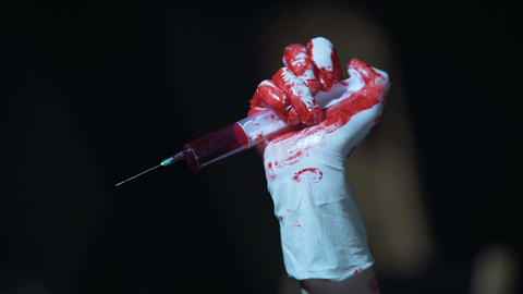 Crazy murderer holding syringe with dripping blood and enjoying terrible view Footage