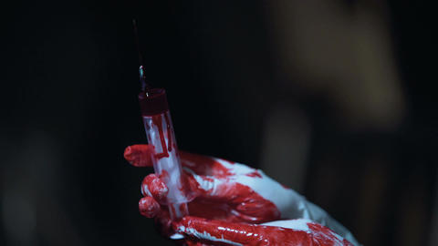 Crazy nurse holding a syringe with blood in hands, horror scene, close up Footage