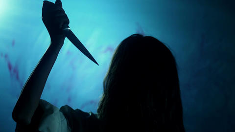 Bloody dark-haired murderer stabbing victim with knife, darkness and horror Live Action