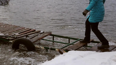 Woman walking dangerously on a destroyed icy pier Footage
