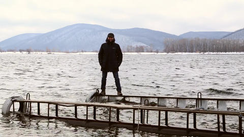Man standing dangerously on a narrow icy pier Footage