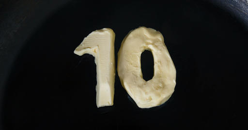 Countdown animation from 10 to 0 of butter in shape of numbers melting on hot pa Footage