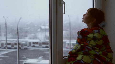 Girl looking out the window at the snowfall GIF