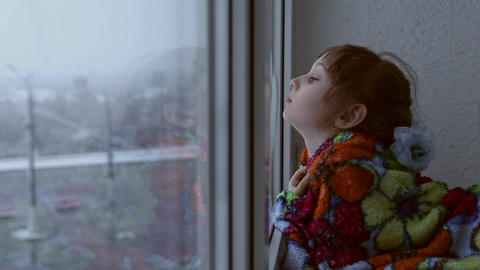 Girl looking out the window at the snowfall Footage