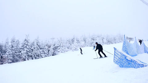 Terrible misty weather on slope in winter mountains. Few skiers down hill skiing Footage