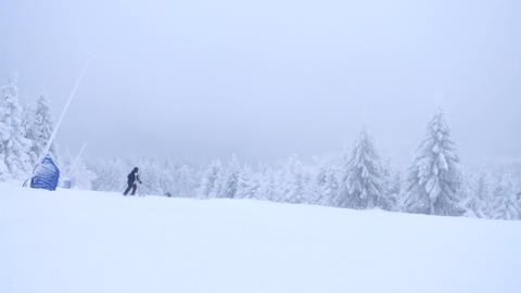 Cold misty weather on piste. Winter ski season in the mountains. Few skiers down Footage