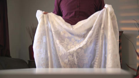Man puts a white cloth on the table Footage
