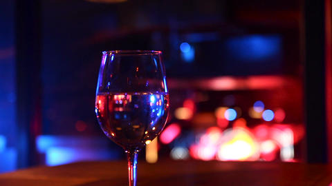 Wine glass on a wooden table at party - Changing defocus to focus Footage
