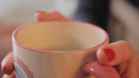 Female hands holding a mug of hot tea Footage