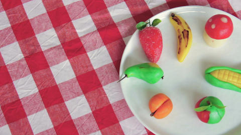 Marzipan fruits are placed on a white plate on a table Footage