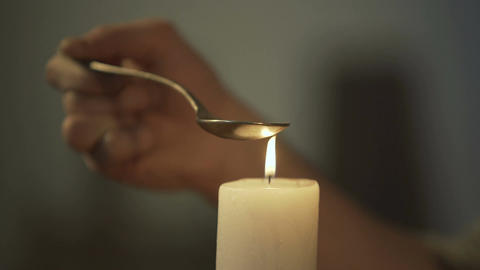 Hand of person heating chemical substance in spoon on candle light, drug abuse Footage