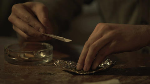 Young man's hands rolling cigarette of medical marijuana to relieve chronic pain Footage