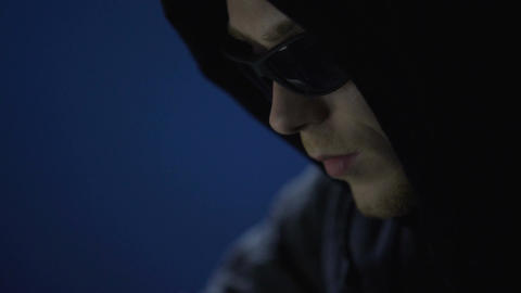 Closeup of man in sunglasses committing crime, illegally using company computer Footage