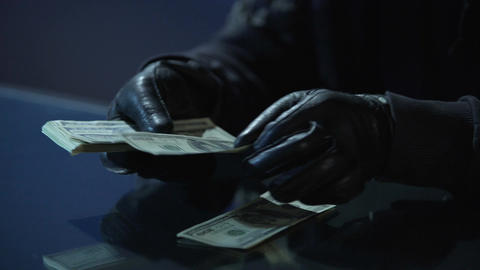Criminal in black gloves counting bundle of money earned for committing crime Footage